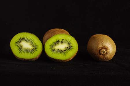 kiwi fruta: Kiwi aislado en el fondo oscuro Foto de archivo