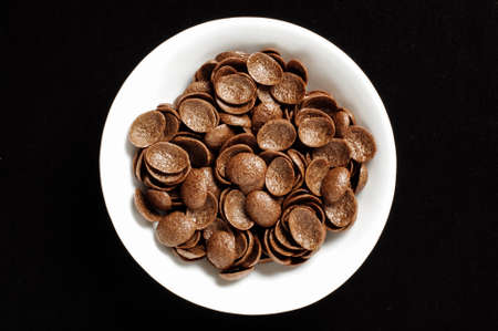 crunch: Bowl of chrispy chocolate crunch cornflakes isolated on the black background