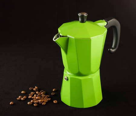 Green coffee maker and coffee beans isolated photo