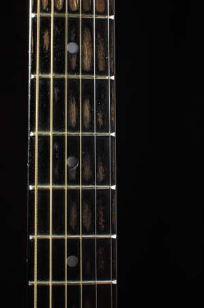 Acoustic guitar fretboard isolated on the dark background photo
