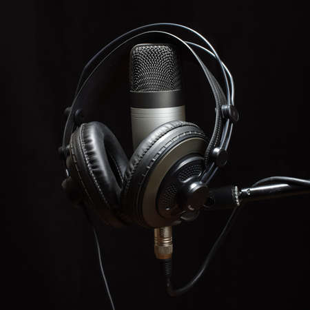 Headphones and condenser microphone isolated on the dark background photo