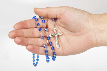 inri: Blue rosary in female palm isolated