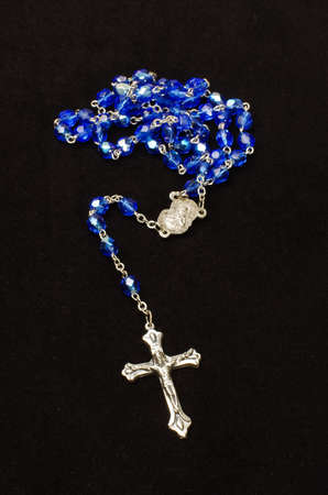 inri: Silver cross crucifix and blue glass rosary isolated