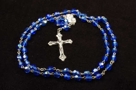 inri: Dominican rosary with Christian cross isolated on the black background
