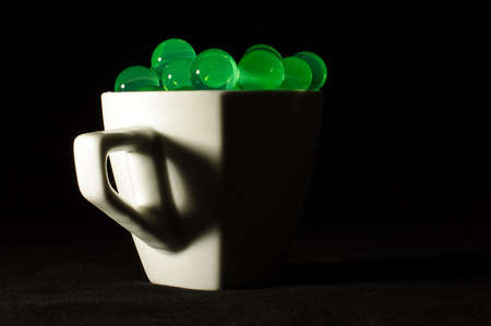 genetically modified organisms: Poison green radioactive bubbles in the mug low key photo Stock Photo