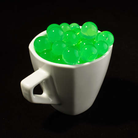 genetically modified organisms: Green transparent bubbles in the white coffee mug Stock Photo