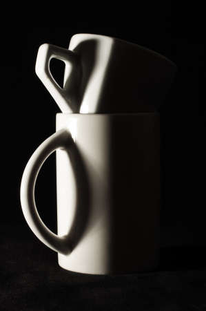Small coffee cup in bigger tea cup in the darkness Stock fotó