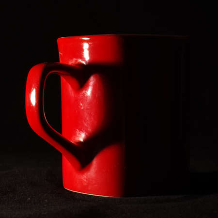 Heart shape shadow on red tea mug isolated on the dark background photo