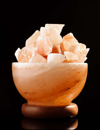 Himalayan salt lamp isolated on the black background photo