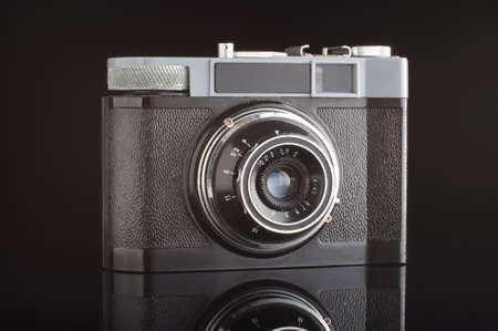 point and shoot: Vintage analogue photo camera isolated with reflection on the black background Stock Photo