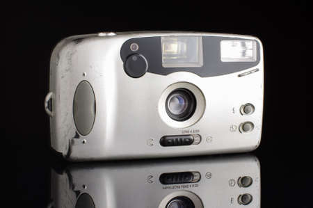 point and shoot: Old used automatic camera isolated on the black background with reflection