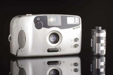 lomography: Old scratched automatic photocamera isolated on the black background with reflection