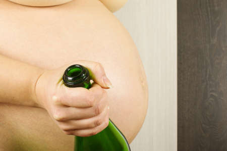 sparking: Pregnant woman holding empty sparking wine bottle Stock Photo