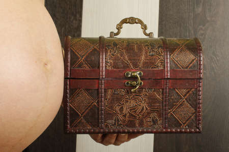 coffer: Pregnant woman holding small coffer