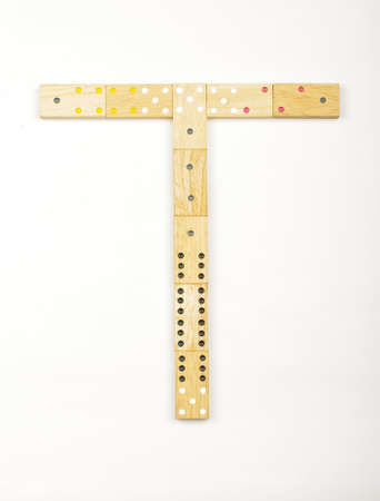 Alphabet letter T arranged from wood dominoes tiles isolated photo