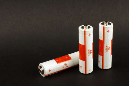 nimh: Three AA batteries isolated on the black background with copy space
