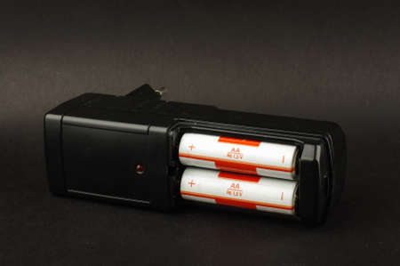 nimh: Black AA battery charger isolated on the black background