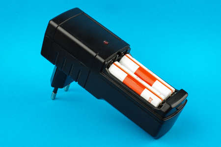 nimh: Black AA batteries charger isolated on the blue background Stock Photo