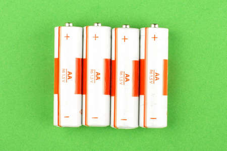electrochemical: White AA batteries isolated on the green background