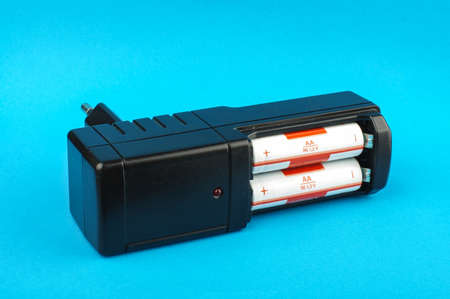 nimh: Black AA battery charger isolated on the blue background