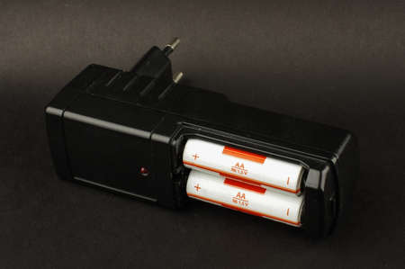 nimh: Black AA battery charger isolated on the dark background Stock Photo