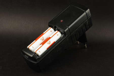 Akkumulátor töltő betöltött akkumulátorok elszigetelt a fekete háttér