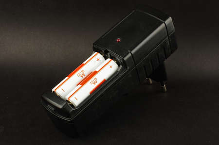 electrochemical: Battery charger with loaded batteries isolated on the black background