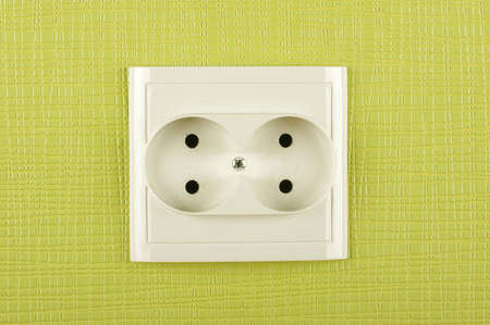 ac: White double non-earthed AC electricity outlet on the green wall