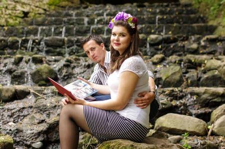 wedding photo album: Young couple sitting near the river with their wedding photo album Stock Photo