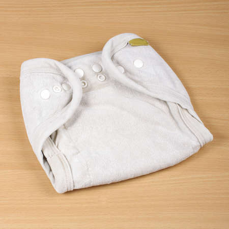 reusable: Natural reusable cloth diaper isolated on the bright wooden background