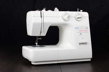 Full automatic sewing machine isolated on the dark background
