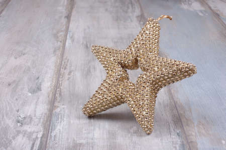 topper: Christmas tree topper decoration golden star isolated on the wooden background Stock Photo