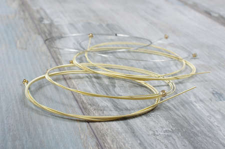 reclaimed: Golden bronze acoustic guitar strings isolated on the reclaimed wood background