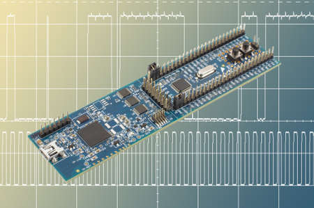 digital signal: Programming hardware evaluation board in front of digital signal oscillogram Stock Photo