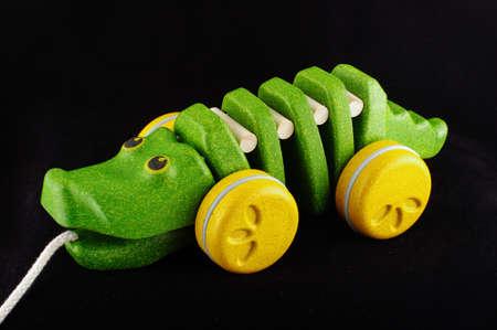 pull toy: Tire lo largo del juguete cocodrilo de madera orgánica aislada en el fondo negro