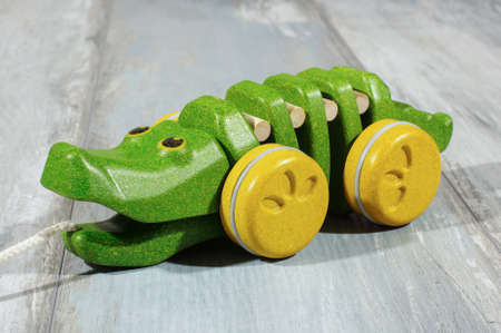 pull along: Pull along organic wooden alligator toy isolated on the reclaimed oak background