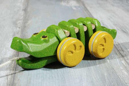 pull toy: Tire lo largo del juguete cocodrilo de madera orgánica aislada en el fondo de roble recuperada