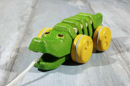 pull toy: Tire lo largo del juguete cocodrilo de madera org�nica aislada en el fondo de roble recuperada