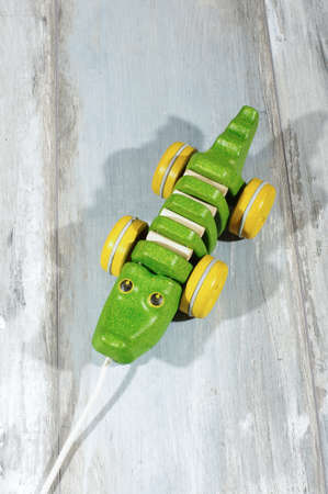 reclaimed: Pull along organic wooden alligator toy isolated on the reclaimed oak background