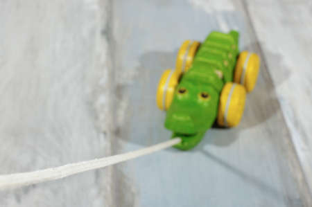pull toy: Pull along organic wooden alligator toy selective focus on a rope Foto de archivo