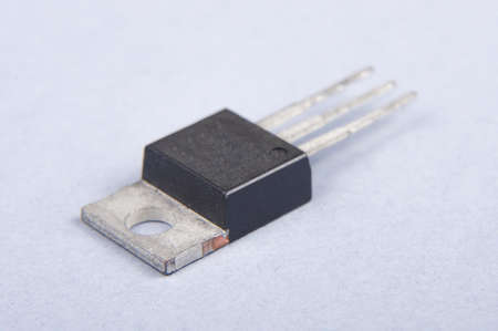 Power transistor in leaded package isolated on the gray background
