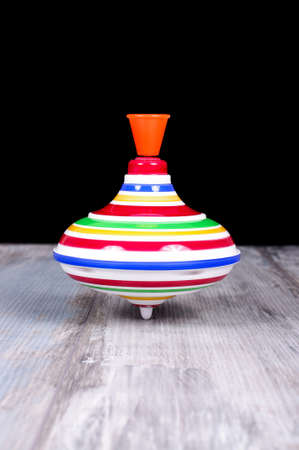 spinning top: Plastic spinning top toy isolated on the reclaimed oak surface