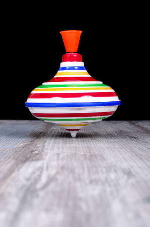 Plastic spinning top toy isolated on the reclaimed oak surface