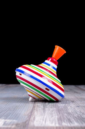 reclaimed: Plastic spinning top toy isolated on the reclaimed oak surface