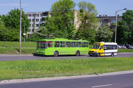 trackless: KAUNAS, LITHUANIA - MAY 27, 2016: Green trolley bus and minibus public transport on the go. Photo taken on May 27, 2016 in Kaunas, Lithuania.