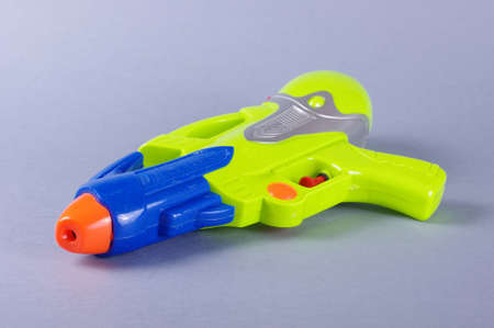 watergun: Water gun toy isolated on the gray background
