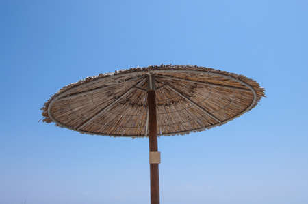 the sun and shade: Thatched sun shade umbrella in the beach of Kos island, Greece Stock Photo