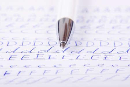 handwrite: Ball point pen tip over alphabet letters background