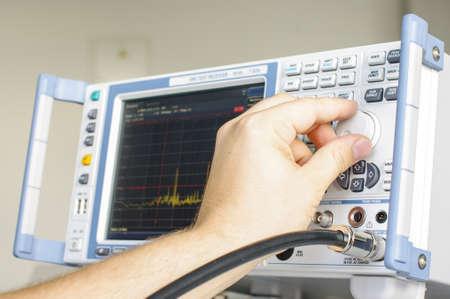 EMC engineer hand adjusting laboratory test receiver