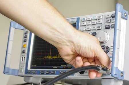 compatibility: EMC technician hand adjusting laboratory test receiver